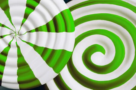 Two bright green and white lollipop closeup as background for design