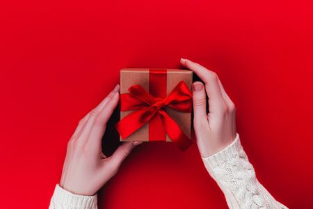 Greeting card with female hands and a gift box with a bow on red background, place for your text.
