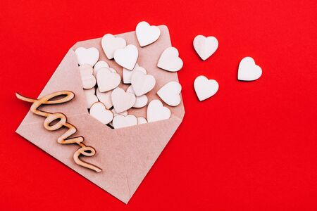 Wooden hearts and inscription Love in an open craft envelope with place for text, holiday of love on red background