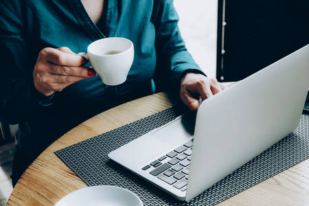 Female hands holding a cup of coffee in a cafe near a laptop, working atmosphere