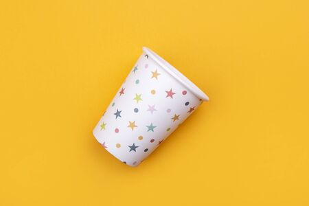 Cardboard coffee glass with colored stars on bright yeloow background