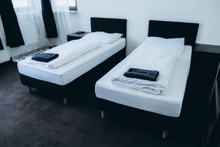 Two beds in a room with white walls, clean hotel room