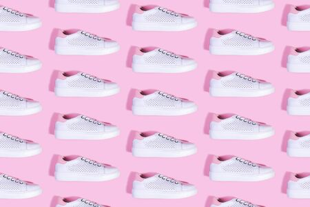 Pure white sneakers on a bright pink background pattern