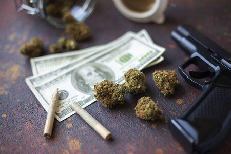 Black gun, marijuana cones and dollar bills on a dark table