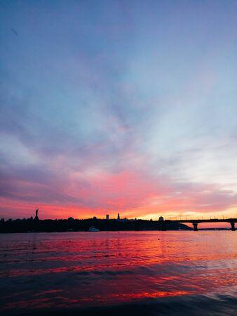 High bridge, river, ships and bright sunset. Beautiful sunset at the bridge. Kiev, Ukraine