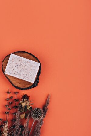 Natural bar of soap on wood cut with dried flowers - beauty treatment on peach background with place for text