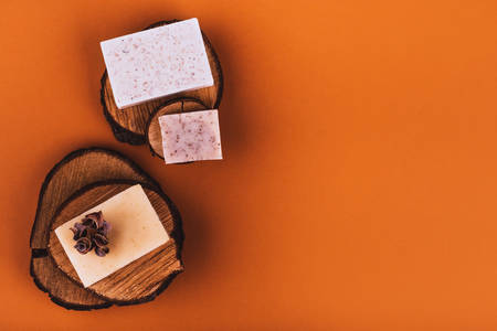 Natural bar of soaps on wood cuts with place for text - beauty treatment on colored background Banco de Imagens
