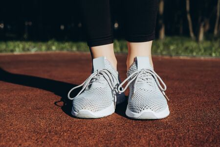 Gray woman sneakers on bright sportsground close-up, sport time Imagens
