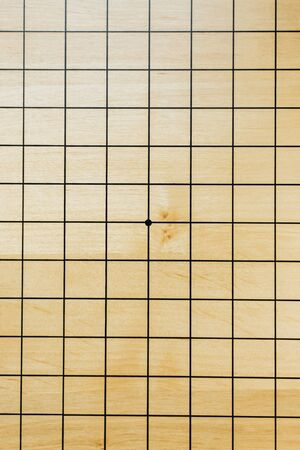 Empty go board, goban - black lines on a wooden product with a dot in the middle with place for text