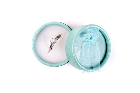 Silver ring with a stone in a turquoise box with a bow isolate on a white background