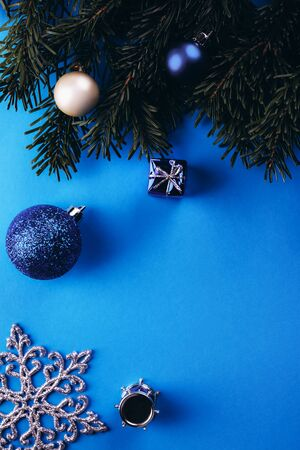 Christmas tree branches, Christmas blue and silver toys in color of the year 2020 on a blue background with place for text.