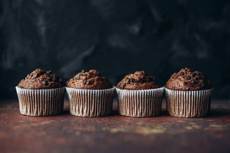 Beautiful chocolate muffins with pieces of chocolate on dark background with place for text