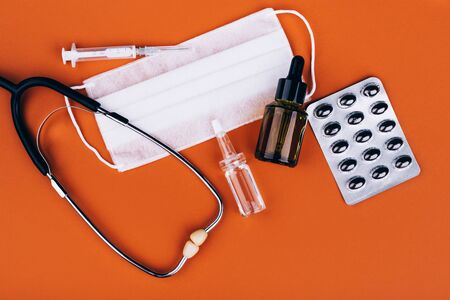 Pills, stethoscope, syringe, glass jar, and a white mask on orange background with place for text
