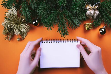 Female hands hold an open white notebook for text near Christmas tree branches and Christmas golden toys on orange background