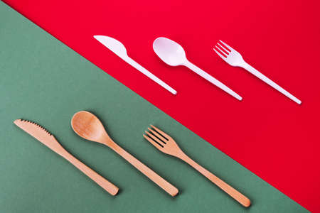 Bamboo spoon, fork and knife on a green background and plastic cutlery on a red background, eco concept Stok Fotoğraf