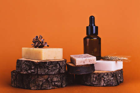 Natural bar of soaps on wood cuts, jar with oil and wheat ear - beauty treatment on colored background Stok Fotoğraf