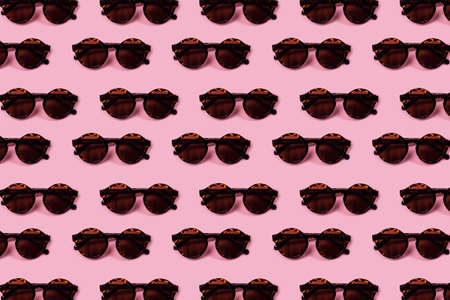 Dark round glasses in a leopard pattern on a light pink background