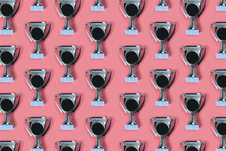 Golden winner cup as trophies pattern on bright pink background with place for text