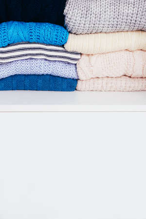 A stack of varied blue sweaters lie on a white wooden background with place for text Stok Fotoğraf