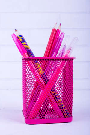 A variety of pink stationery in a stand on a white background with place for text