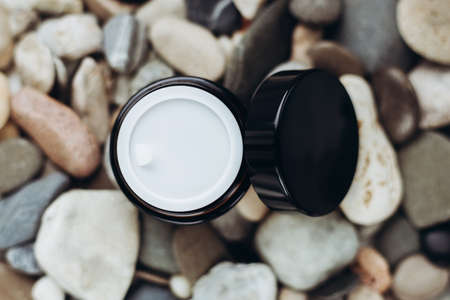 Jar of cosmetic cream with open lid on different stone background close-up with place fr text