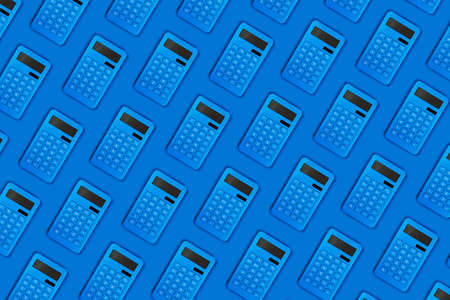 Bright blue calculators on a blue background pattern close-up for your design