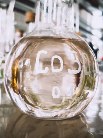 Transparent chemical substance in a transparent flask on a laboratory background