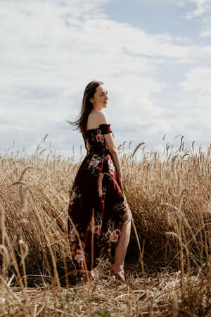 Beautiful young woman in a dress stands in a wheat field