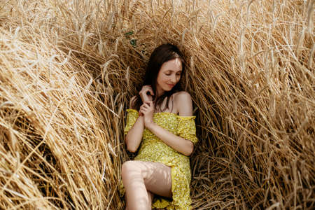 Beautiful young woman in yellow dress lies in a wheat field Stok Fotoğraf
