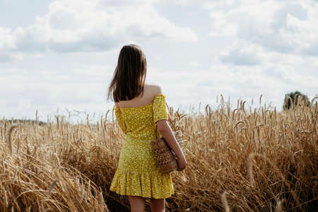 Beautiful young woman in yellow dress stands back with a basket in a wheat field