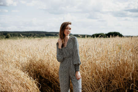 Beautiful young woman in colored overalls standing in a wheat field