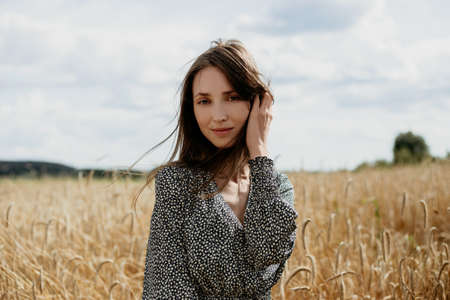 Portrait of beautiful young woman in colored overalls in a wheat field Stok Fotoğraf