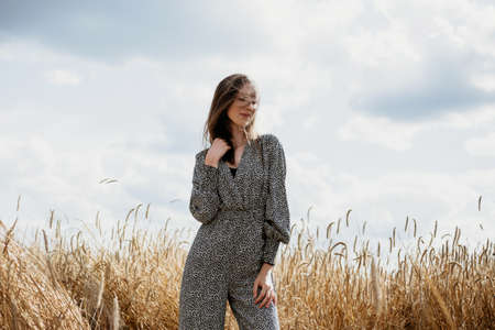 Beautiful young woman in colored overalls with disheveled hair in a wheat field
