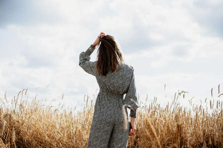 Beautiful young woman in colored overalls standing with his back in a wheat field Stok Fotoğraf