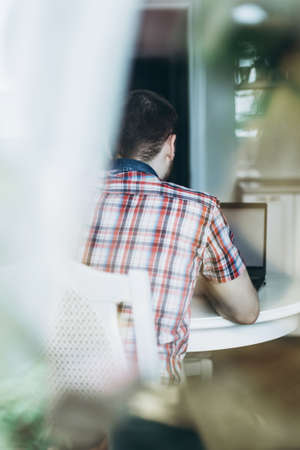 A young man in a plaid shirt sits at a laptop in a bright kitchen with his back to the camera