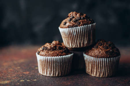 Beautiful chocolate muffins with pieces of chocolate on dark background