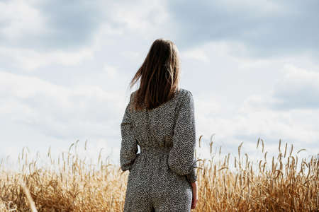 Beautiful young woman in colored overalls stands in a wheat field
