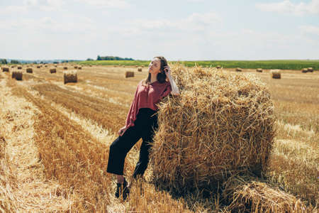 Beautiful young woman in a burgundy blouse and black pants leans on a haystack with her eyes closed in a field Stok Fotoğraf