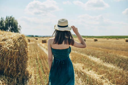 Beautiful young woman in green dress stands in a wheat field holding a straw hat on the background of haystacks Stok Fotoğraf