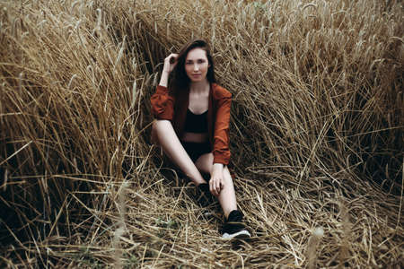 Beautiful young woman in brown shirt sitting in a wheat field and looking into the camera