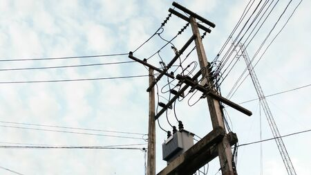electric current: local electric pole with  have one transformers to convert electric current to low voltage on blue sky with cloud background.
