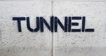 Text TUNNEL by spraying on the cement wall.