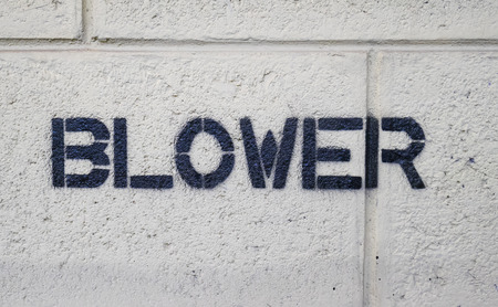 Text BLOWER by spraying on the cement wall.