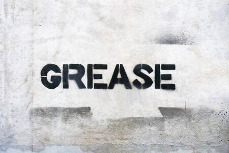 Text GREASE by spraying on the cement wall. Stok Fotoğraf