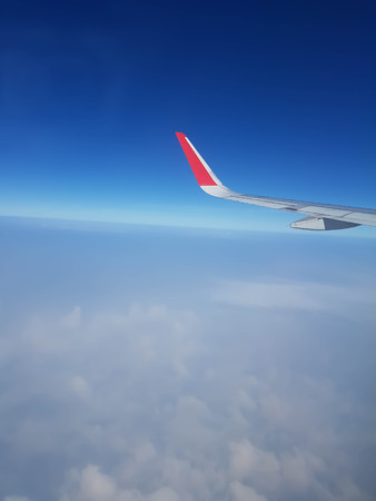 Clouds, sky and wing aeroplane as seen through window of an aircraft
