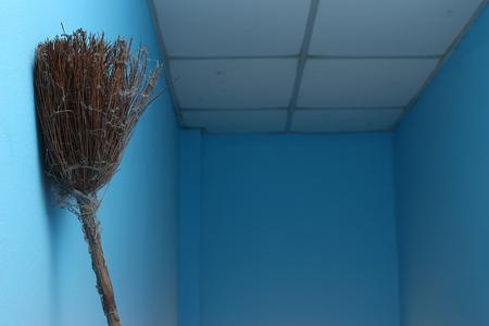 壁、天井を背景に蜘蛛の巣ほうきもたれ。