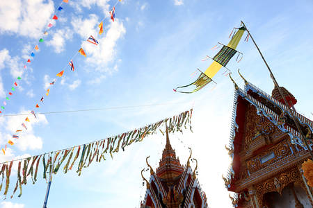 In this picture, It is a tradition of Thai people, Buddhist merit., Banknotes are sewn together, The flag is mixed together, Sorted in a beautiful row, Tie up on the roof of the church. Stock Photo