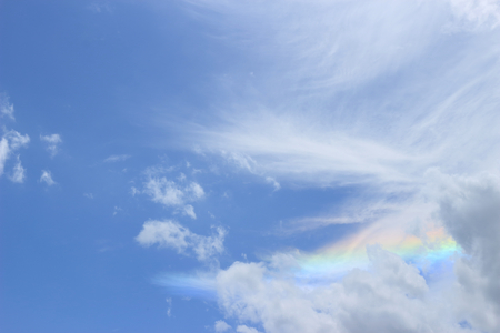 The sky with cumulus clouds and  there is a rainbow across.