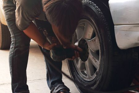 The mechanic is using an air wrench to remove or insert female bolts. To lock the wheel into the gray car wheel hub. Stok Fotoğraf