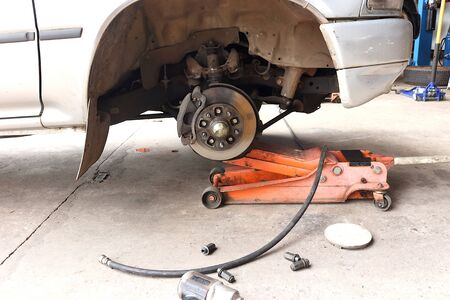 Gray car with the right front wheel removed. You can see the brake discs and other suspension equipment inside. There was a hydraulic floor jack that lift up the car. There are air wrence, air hose, bolts and hub caps in the front of picture.